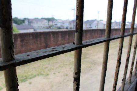 25.鉄格子越しに見える塀の外の世界の写真