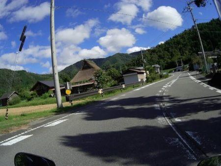 県道19号線沿いの茅葺屋根の家の写真